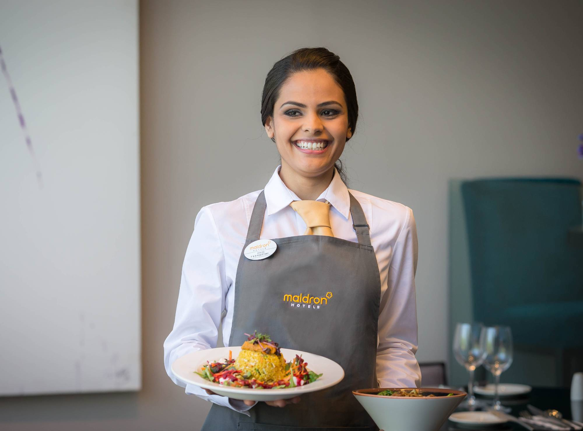 smiling waitress serving freshly prepared dishes Grain and Grill Restaurant Maldron Hotels
